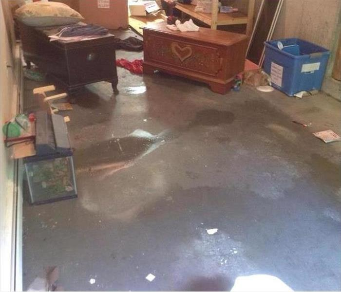 water on concrete floor in a basement, contents around